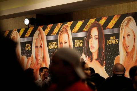 Crowds walk past a banner advertising adult film stars at AVN's Adult Entertainment Expo at the ...