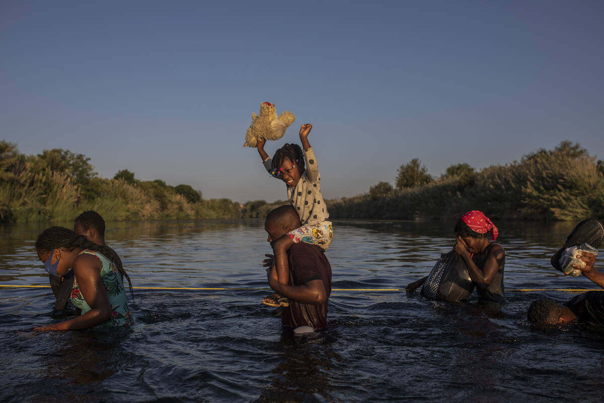 A little girl holds her stuffed animal high above the water as migrants, many from Haiti, wade ...