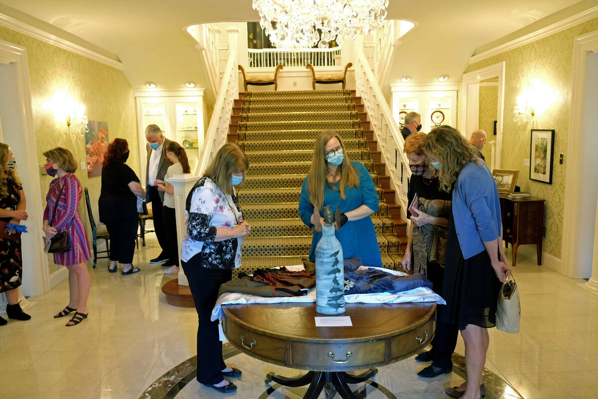 Visitors look at fabrics on display Monday as part of an exhibit in the governor's mansion in C ...