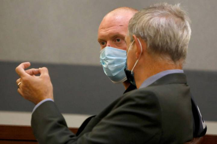 New Haven police officer Robert Ferraro, face to camera, listens to his attorney Gabriel Grasso ...