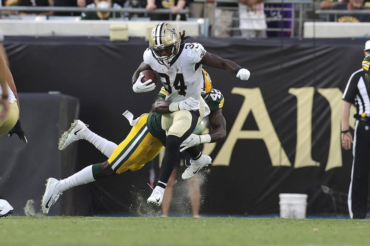 New Orleans Saints running back Tony Jones (34) and Green Bay Packers inside linebacker Oren Bu ...