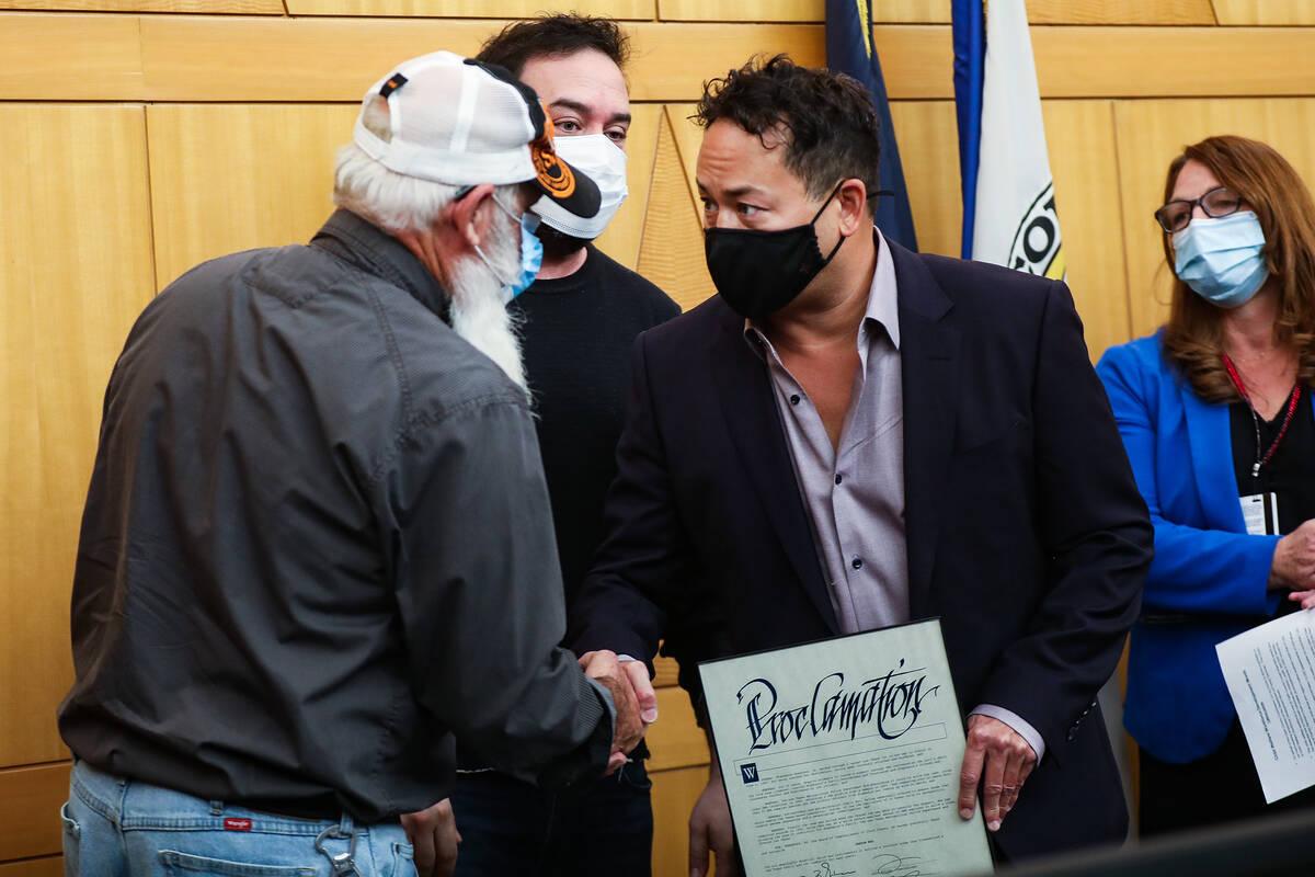 John Isaacson, left, shakes hands with philanthropist Justin Woo, right, as Othram CEO David Mi ...