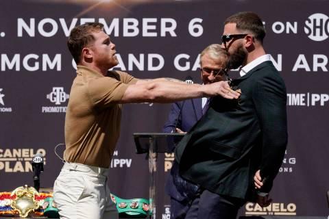 Unified WBC/WBO/WBA super middleweight champion Canelo Alvarez, left, shoves undefeated IBF Sup ...