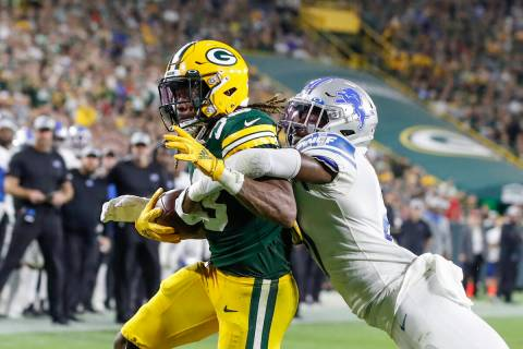 Green Bay Packers running back Aaron Jones, left, scores a touchdown as he is tackled by Detroi ...