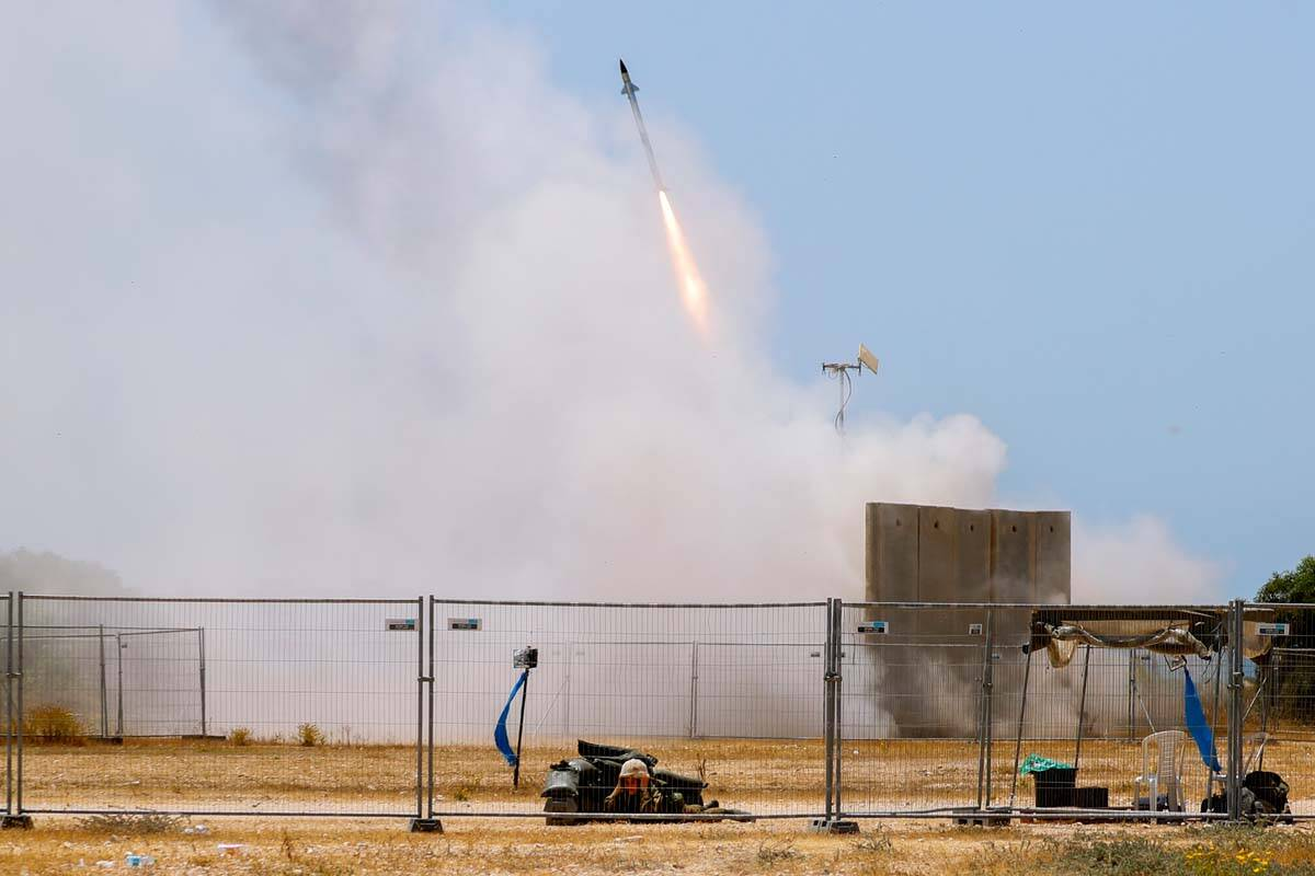 A Israeli soldier takes cover as an Iron Dome air defense system launches to intercept a rocket ...