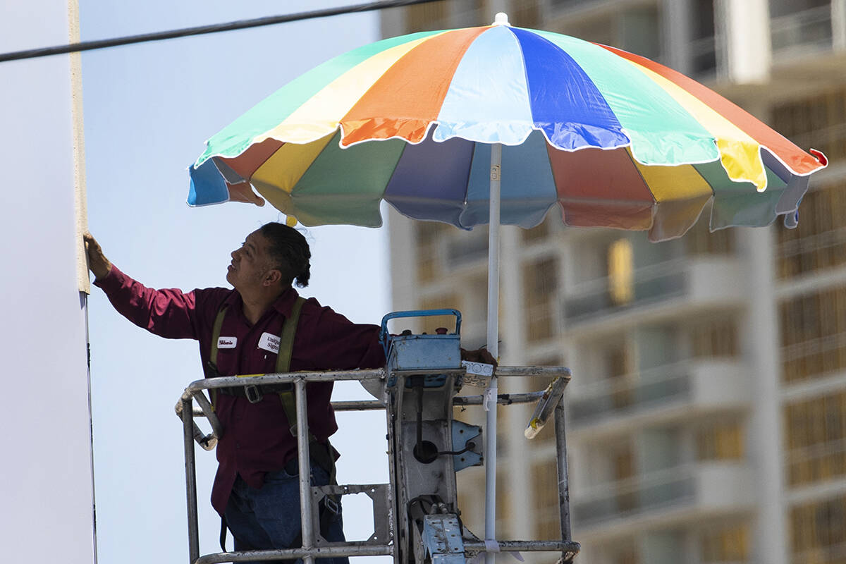 A worker uses a giant umbrella to protect himself from sun as he works on an outdoor advertisin ...
