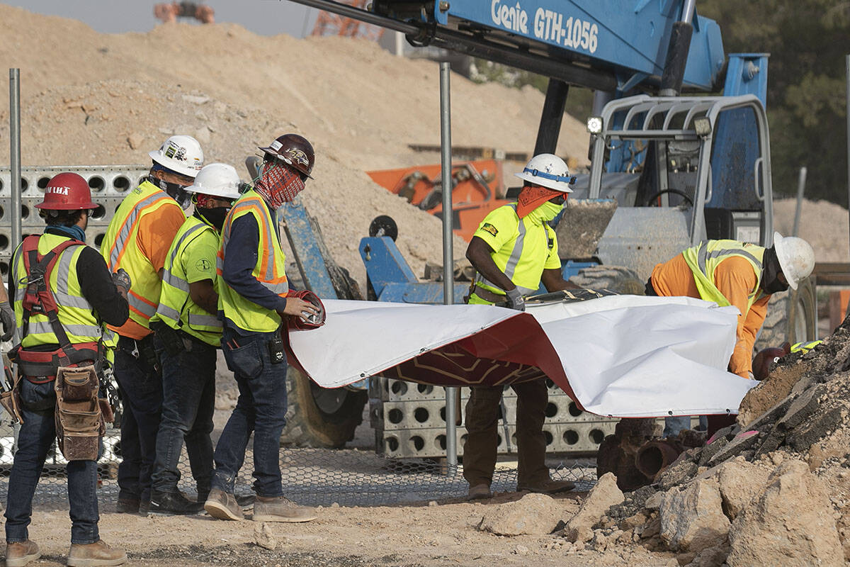 Construction workers try to recover the Resorts World construction site sign after heavy wind k ...