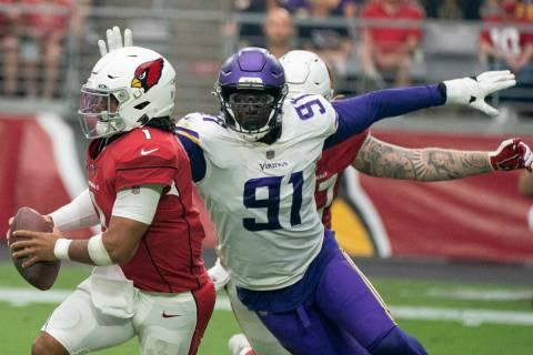 Arizona Cardinals' Kyler Murray 1,runs away from Minnesota Vikings' Stephen Weatherly 91, durin ...