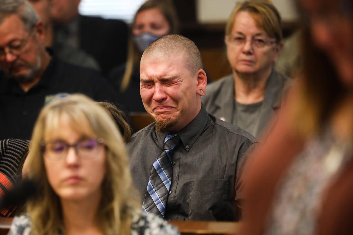 Michael Jenkins, eldest son of slain Nevada Highway Patrol Sgt. Ben Jenkins, reacts as his moth ...