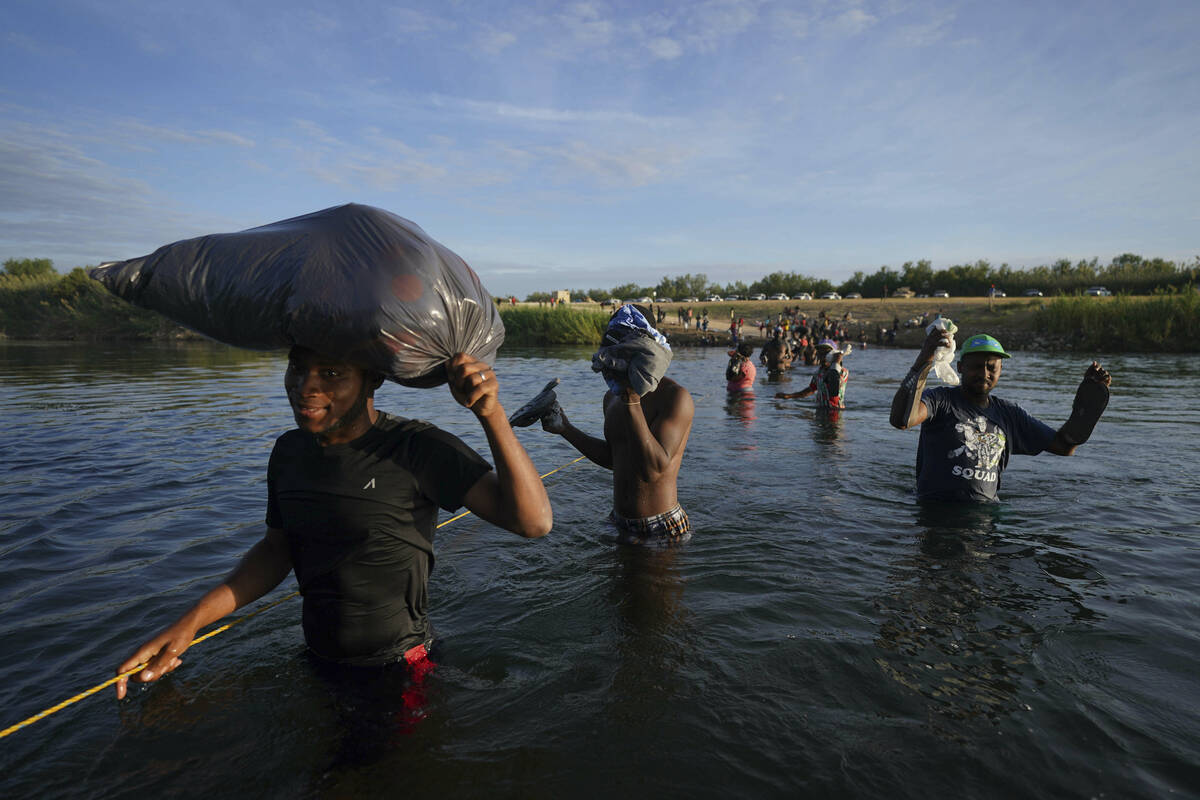 Migrants, many from Haiti, wade across the Rio Grande river to leave Del Rio, Texas, and return ...