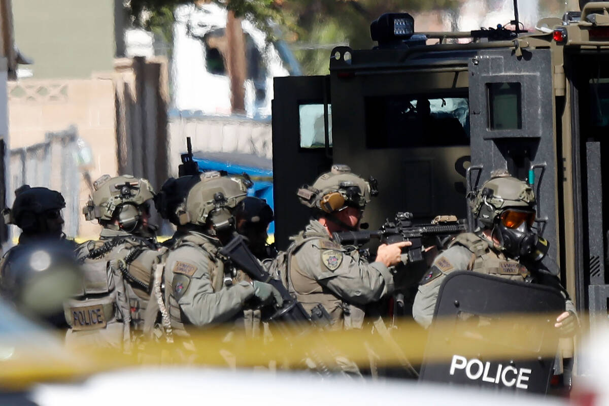 Members of the SWAT team gather around a house in the 300 block of South 11th Street, Tuesday, ...