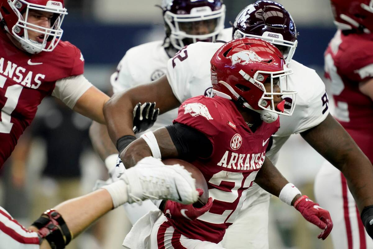 Arkansas running back Trelon Smith (22) carries the ball as Texas A&M defenders give chase in t ...