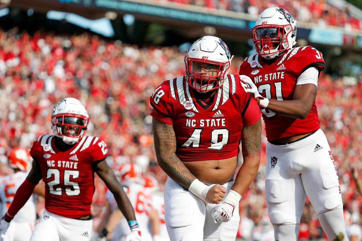 North Carolina State's Cory Durden (48) celebrates a sack with teammate Khalid Martin (21) and ...