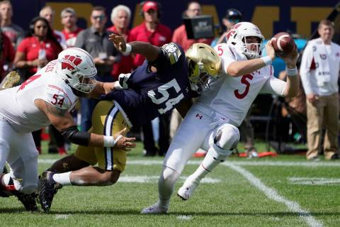 Wisconsin quarterback Graham Mertz (5) makes a two-handed pass to avoid the pressure from Notre ...