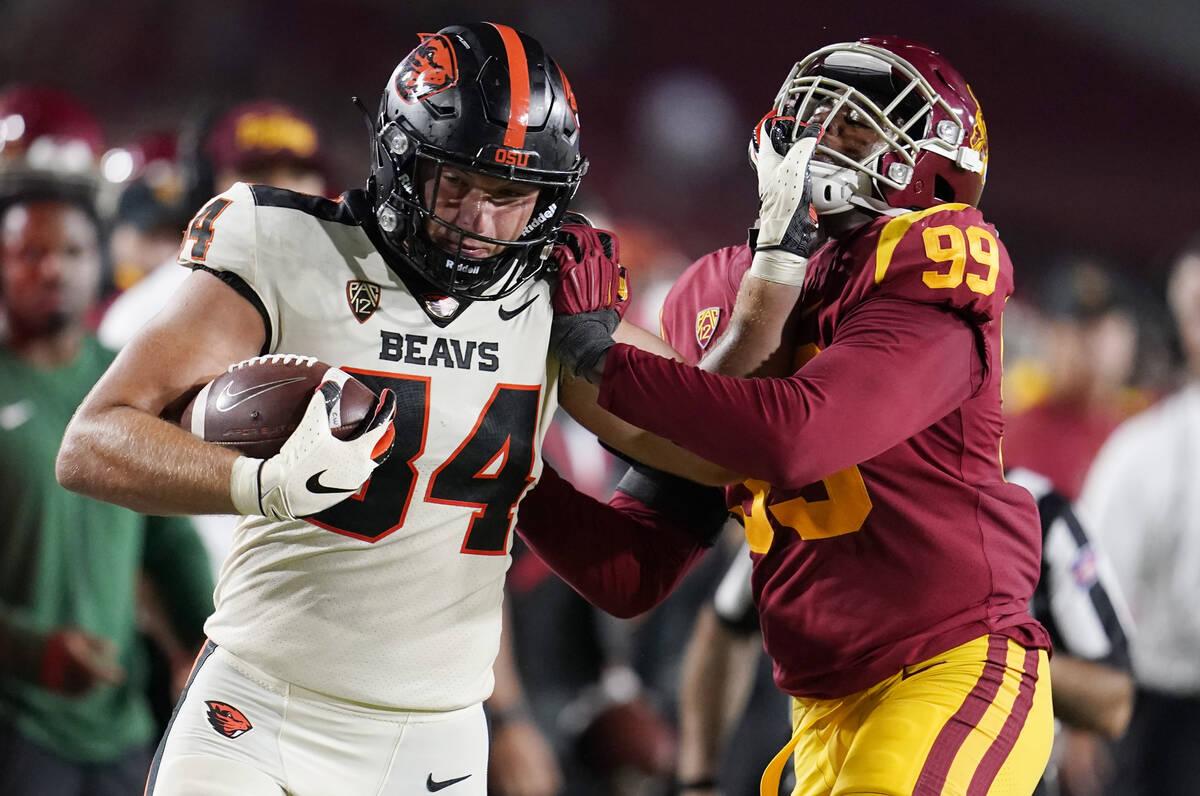 Oregon State tight end Teagan Quitoriano (84) stiff-arms Southern California linebacker Drake J ...