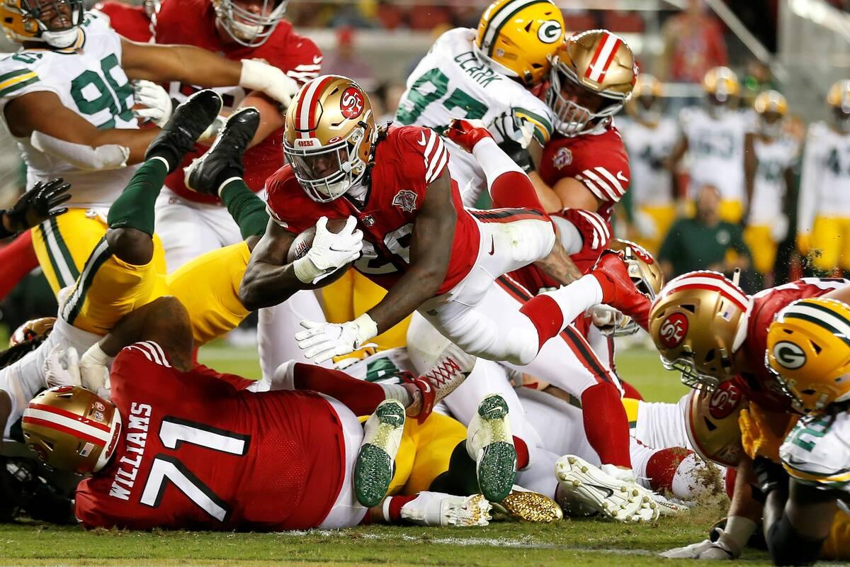 San Francisco 49ers running back Trey Sermon, middle, runs for a touchdown against the Green Ba ...