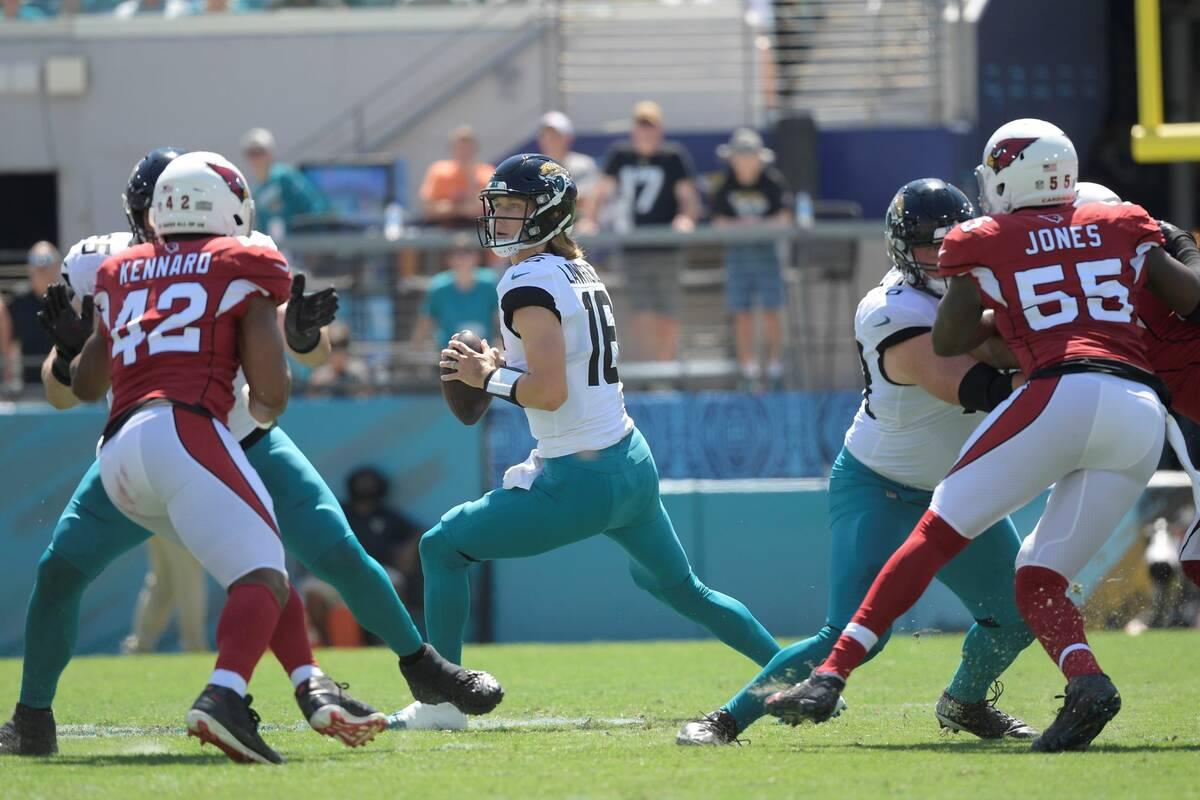 Jacksonville Jaguars quarterback Trevor Lawrence (16) looks for a receiver as Arizona Cardinals ...