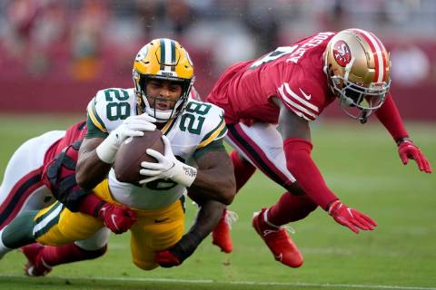 Green Bay Packers running back A.J. Dillon (28) is tackled by San Francisco 49ers linebacker Az ...