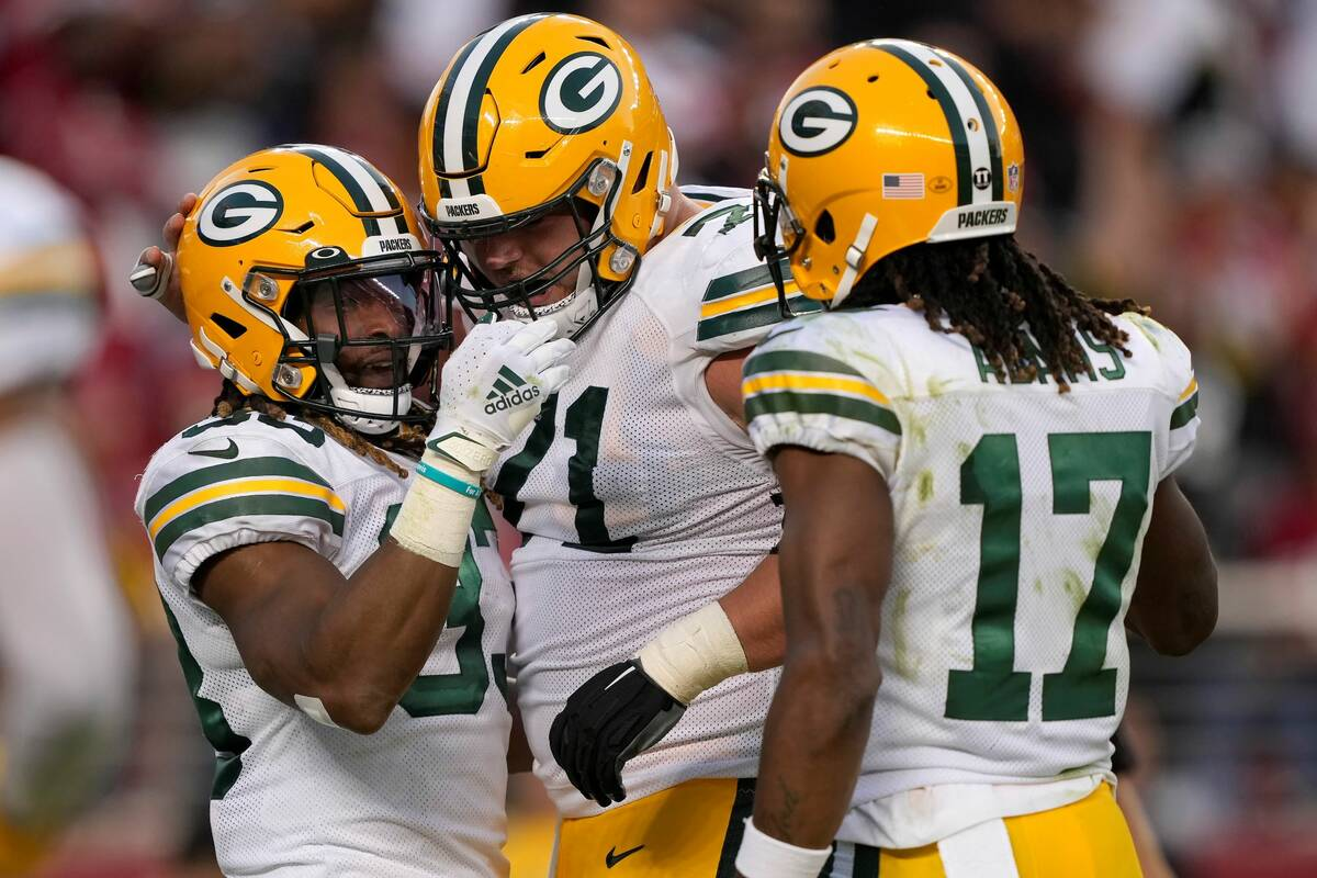 Green Bay Packers running back Aaron Jones, left, is congratulated by center Josh Myers, middle ...