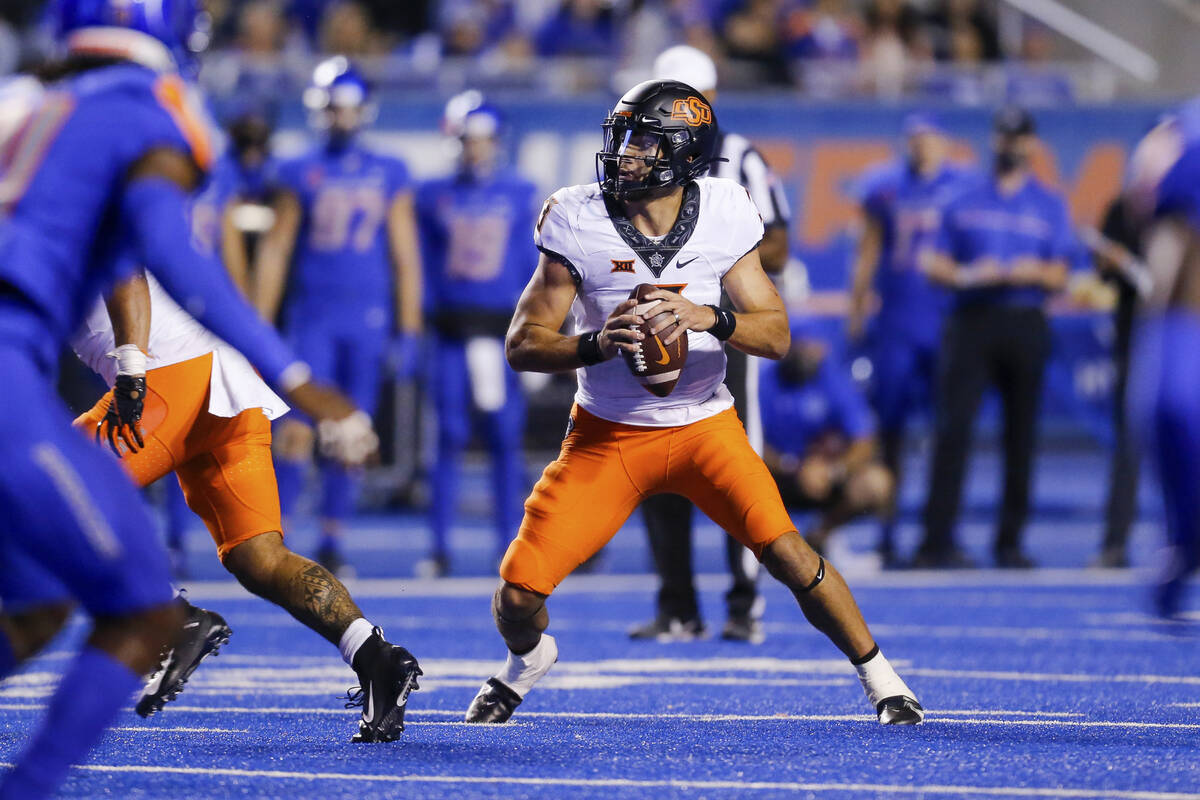 Oklahoma State quarterback Spencer Sanders drop back during the second half of the team's NCAA ...