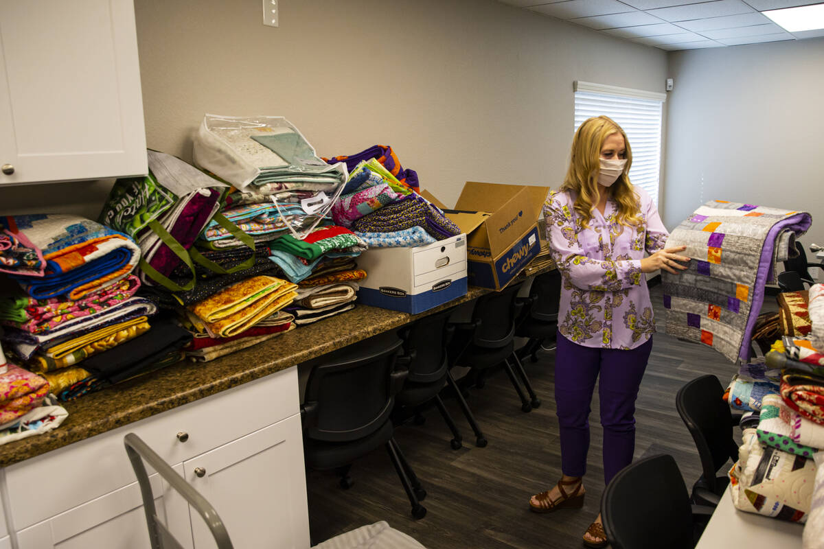 Tennille Pereira, director of the Vegas Strong Resiliency Center, holds a donated quilt featuri ...