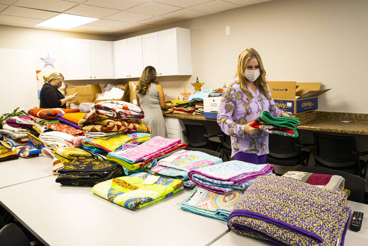 Tennille Pereira, director of the Vegas Strong Resiliency Center, right, looks through donated ...