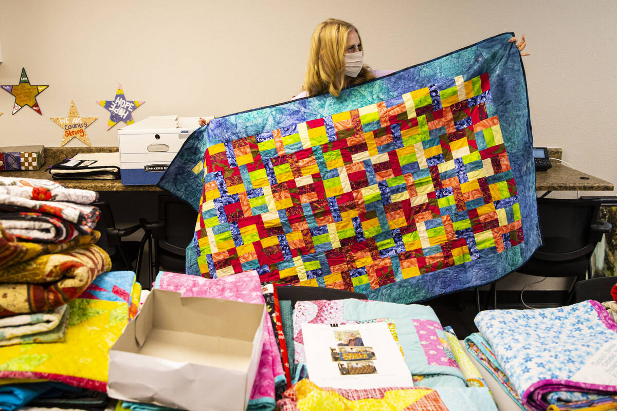 Tennille Pereira, director of the Vegas Strong Resiliency Center, shows a donated quilt created ...