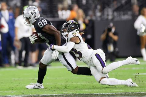 Raiders wide receiver Bryan Edwards (89) is tackled by Baltimore Ravens cornerback Anthony Aver ...