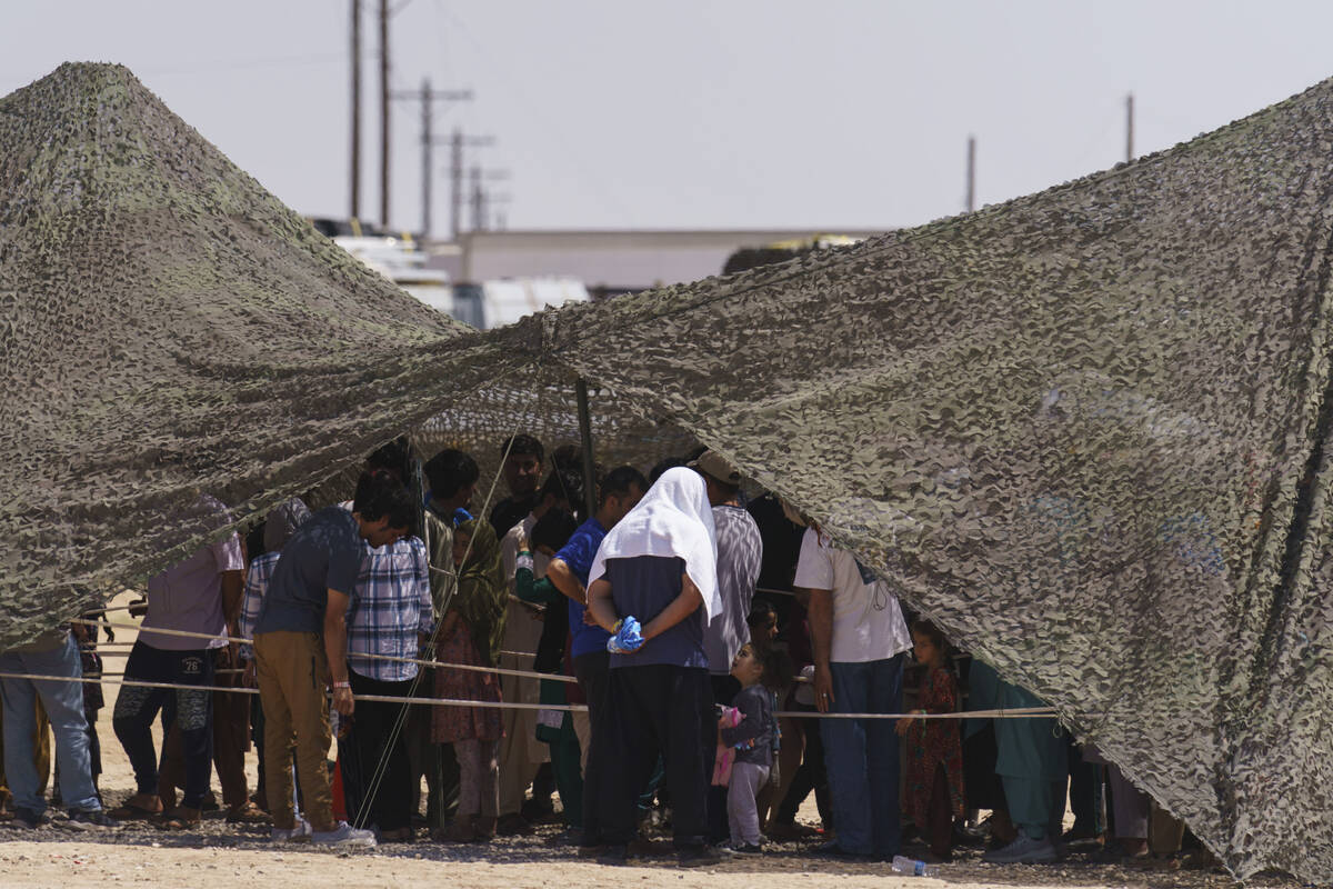 Afghan refugees line up for food outside a dining hall at Fort Bliss' Doña Ana Village where t ...