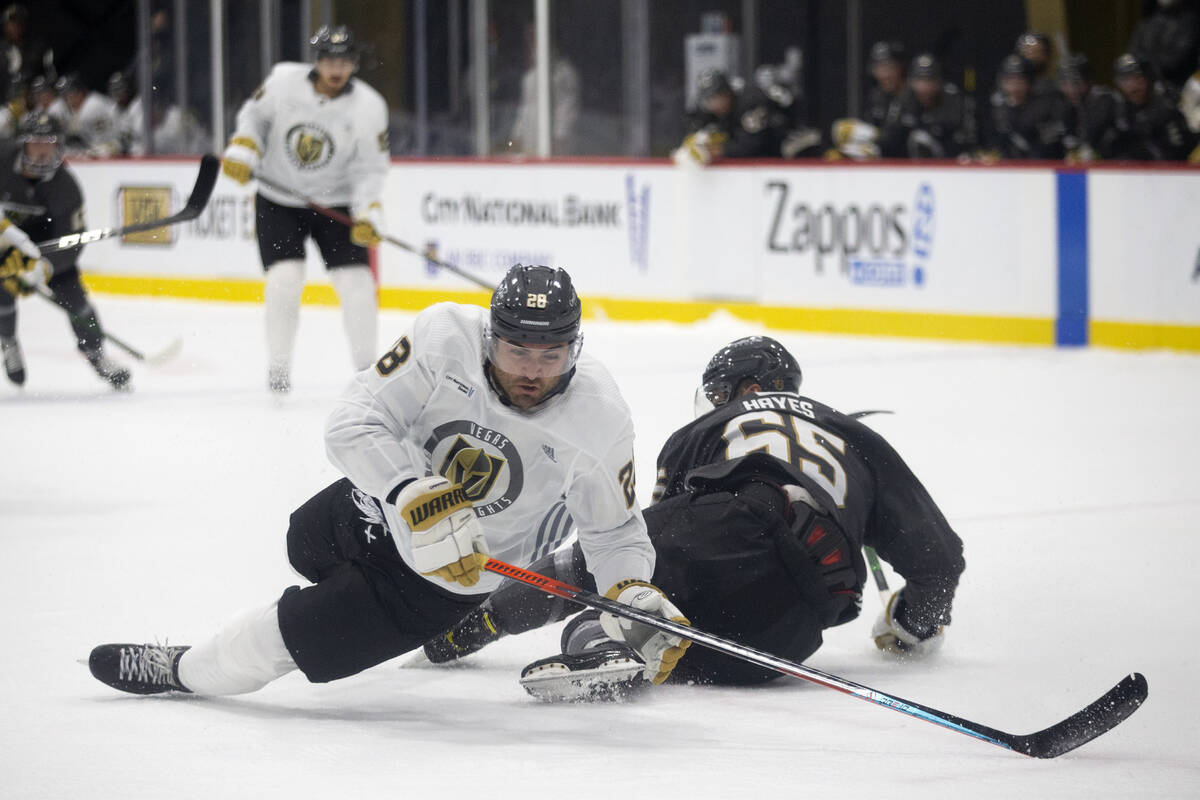Golden Knights left wing William Carrier (28) and defenseman Zack Hayes (65) fall to the ice du ...