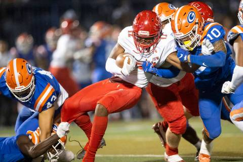 Arbor View's Trae Miller (12) is tackled by Bishop Gorman's Palaie Faoa (10) during the first h ...