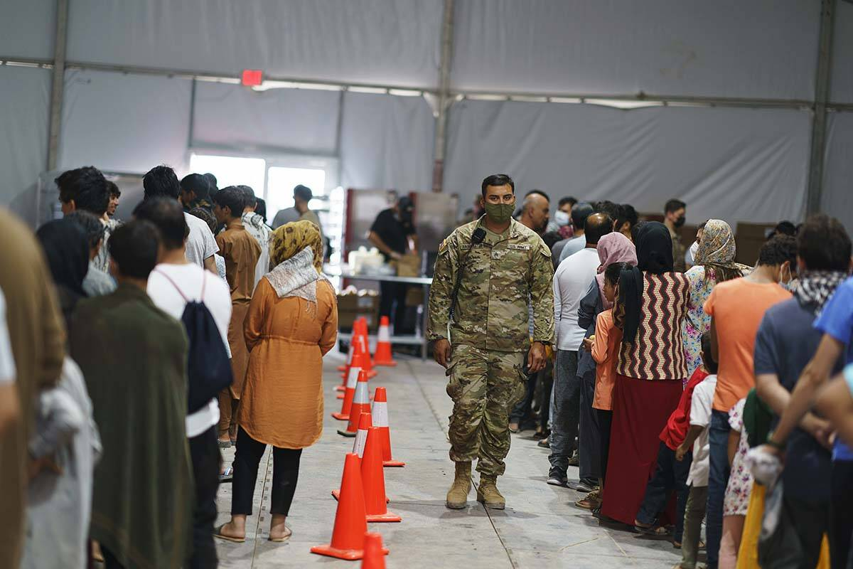Afghan refugees line up for food in a dining hall at Fort Bliss' Doña Ana Village where they a ...