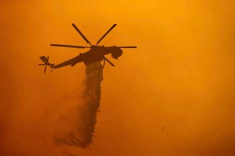 A helicopter drops water on the Fawn Fire burning north of Redding in Shasta County, Calif., on ...