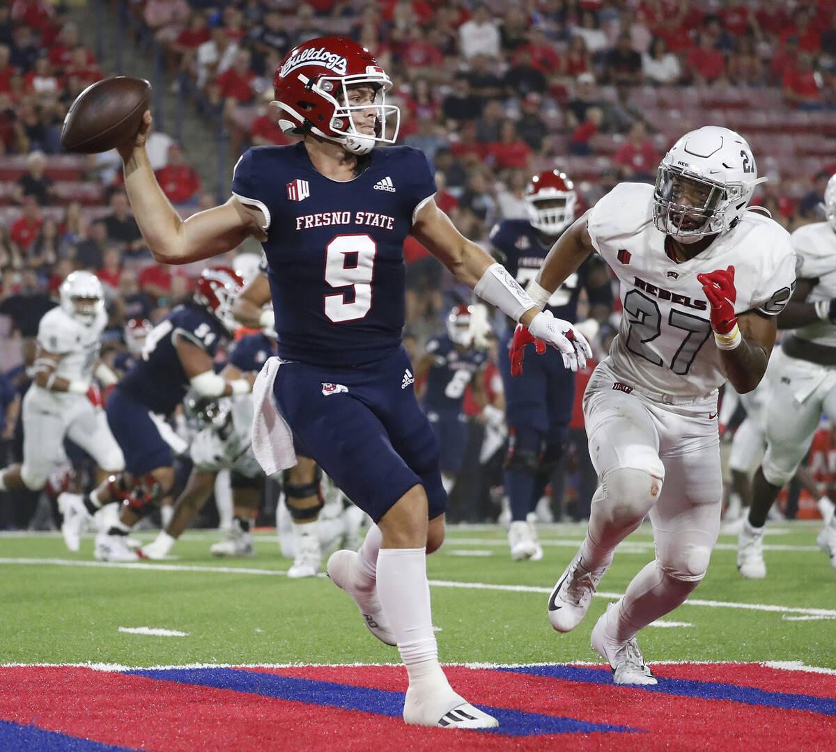 Fresno State quarterback Jake Haener avoids a sack against UNLV linebacker Austin Ajiake during ...
