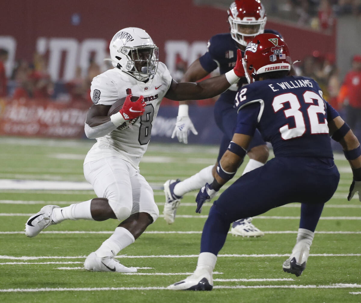 UNLV running back Charles Williams looks to run past Fresno State defensive back Evan Williams ...