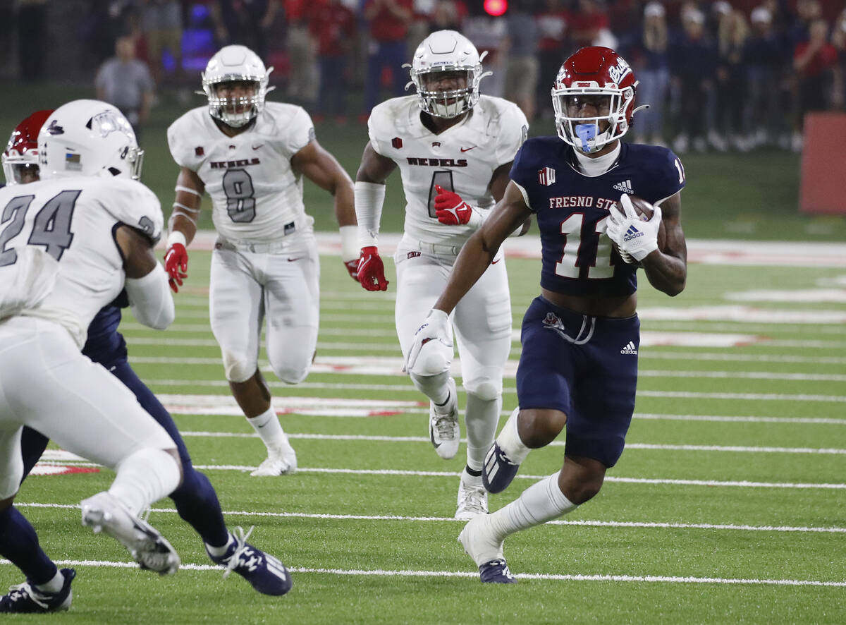 Fresno State wide receiver Josh Kelly runs around UNLV defenders during the first half of an NC ...