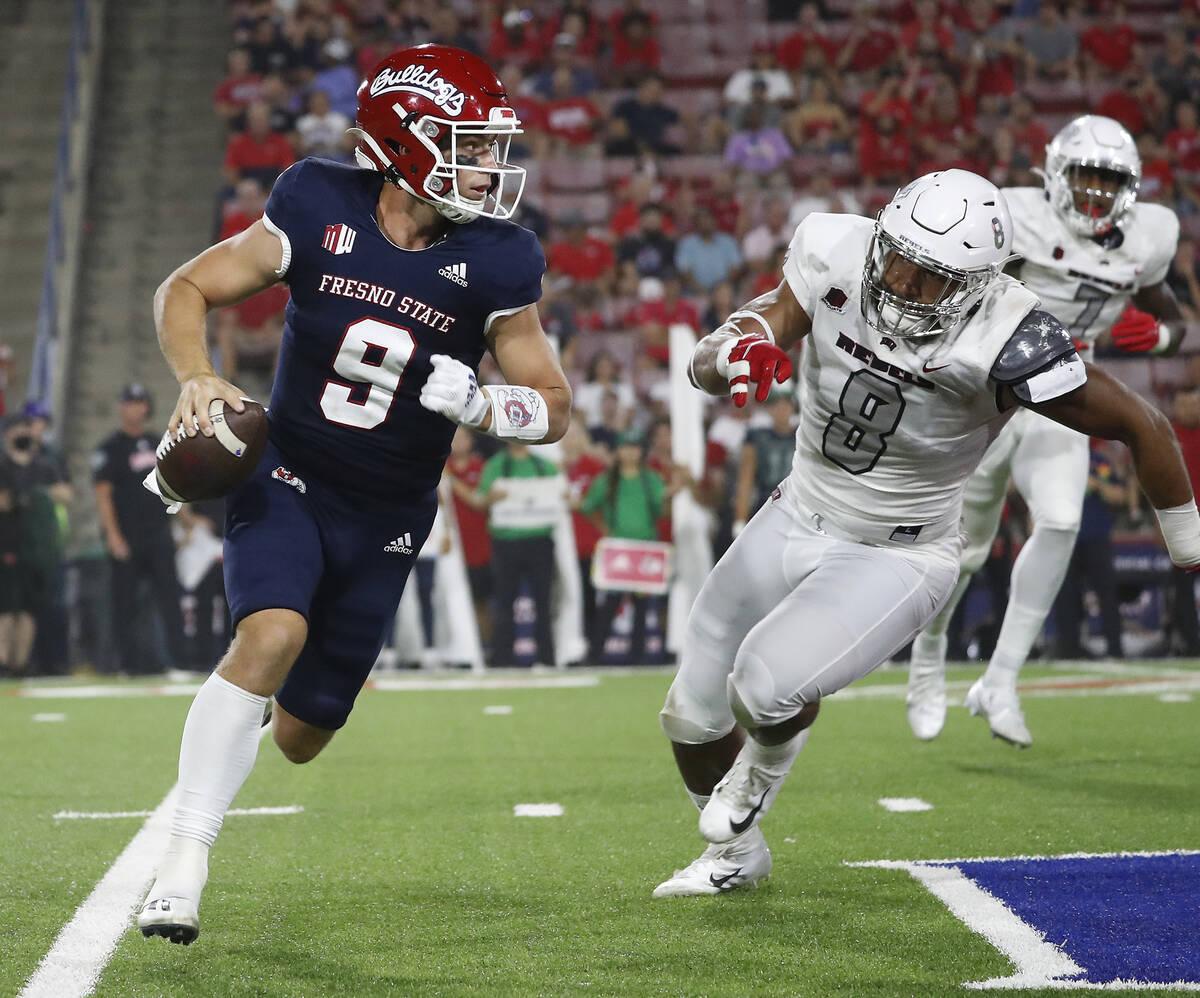 Fresno State quarterback Jake Haener avoids a sack against UNLV linebacker Kylan Wilborn during ...