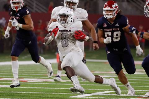 UNLV running back Charles Williams, center, runs for a big gain against Fresno State during the ...