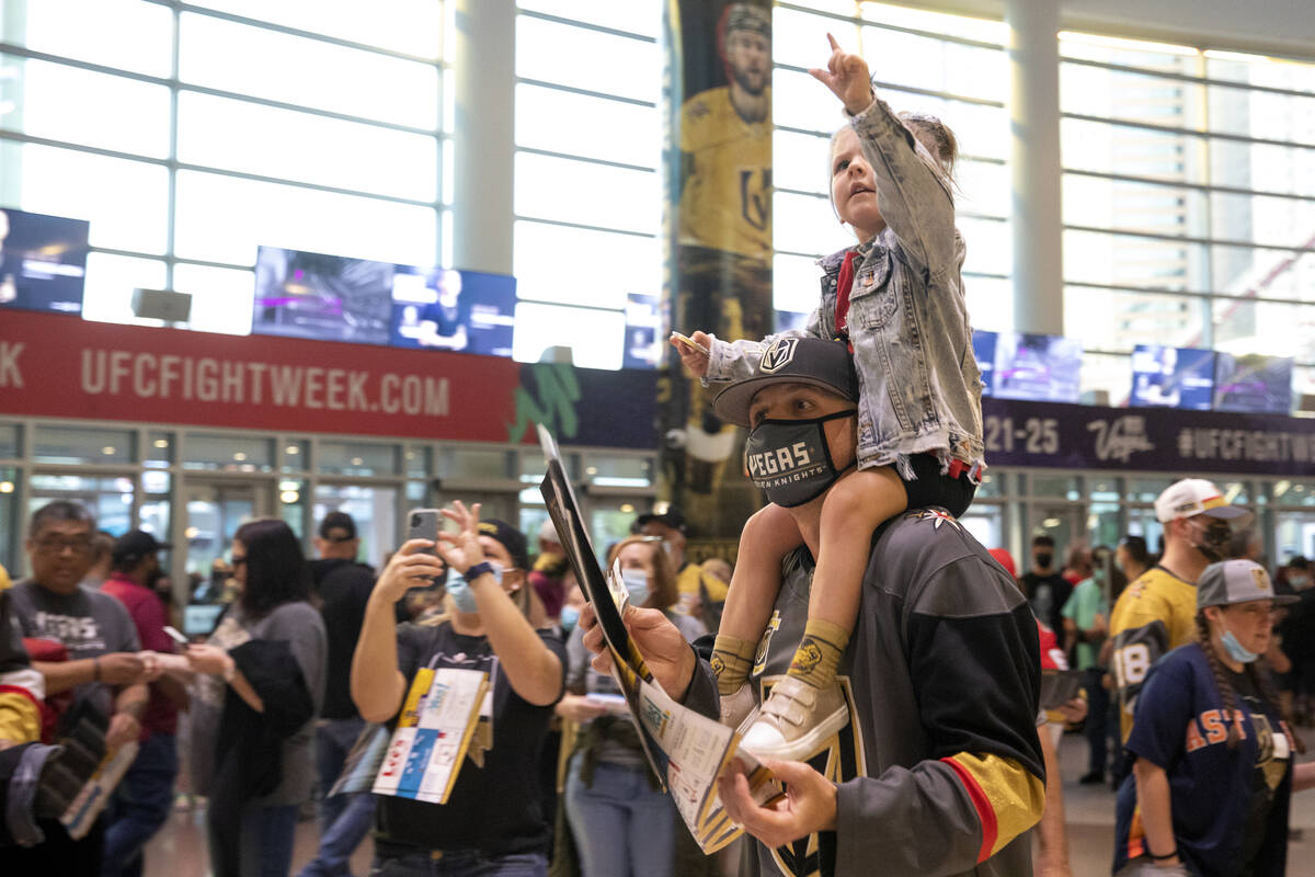 Lennon Wells, 3, sees the pre-game fan parade coming ahead as her father Jake Wells holds her b ...