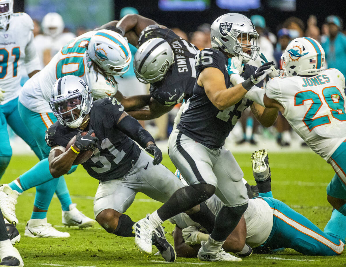 Las Vegas Raiders running back Peyton Barber (31) eyes the end zone on a run past Miami Dolphin ...