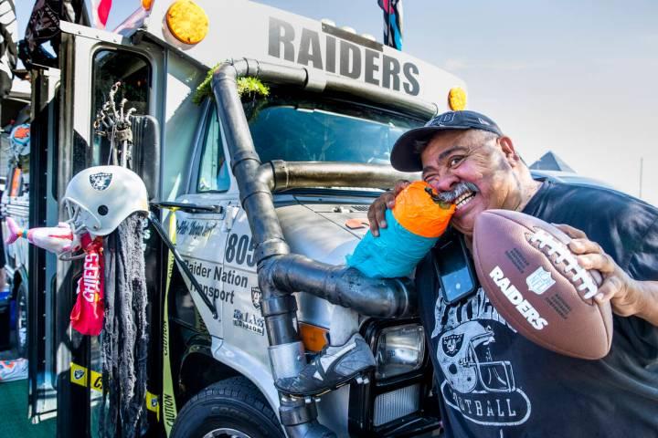 Andy Coronado bites a Miami Dolphins leg attached to his AC12 Raider Nation Bus before the Raid ...