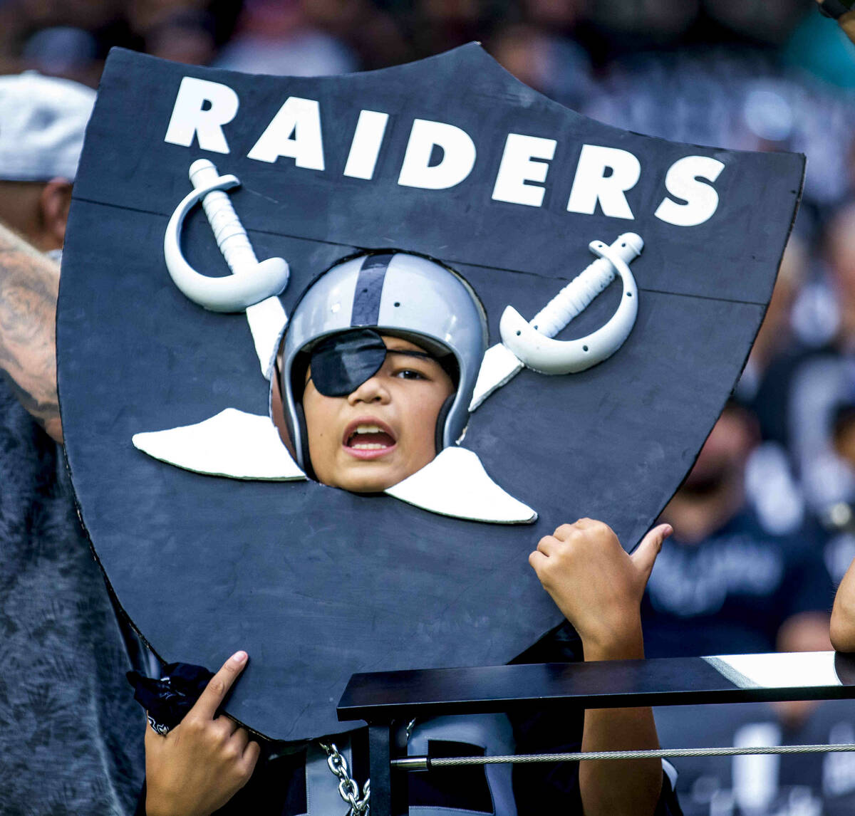 A young Raiders fan wears a homemade shield versus the Miami Dolphins in the first half of thei ...
