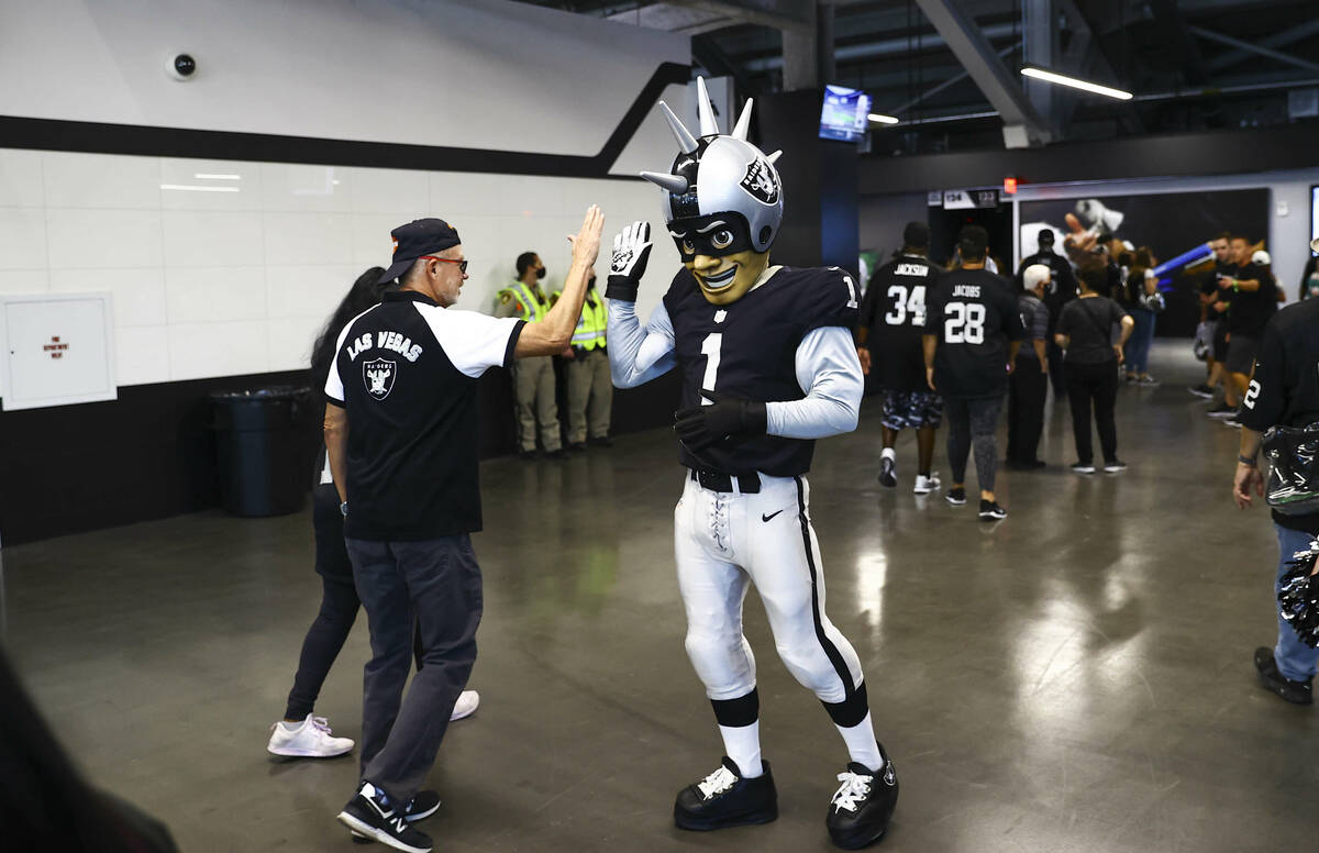 Mascot Raider Rusher greets fans as they arrive at Allegiant Stadium while tailgating before an ...