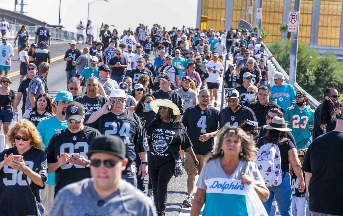 Fans walk across the Hacienda Avenue bridge as the Raiders will face the Miami Dolphins for the ...