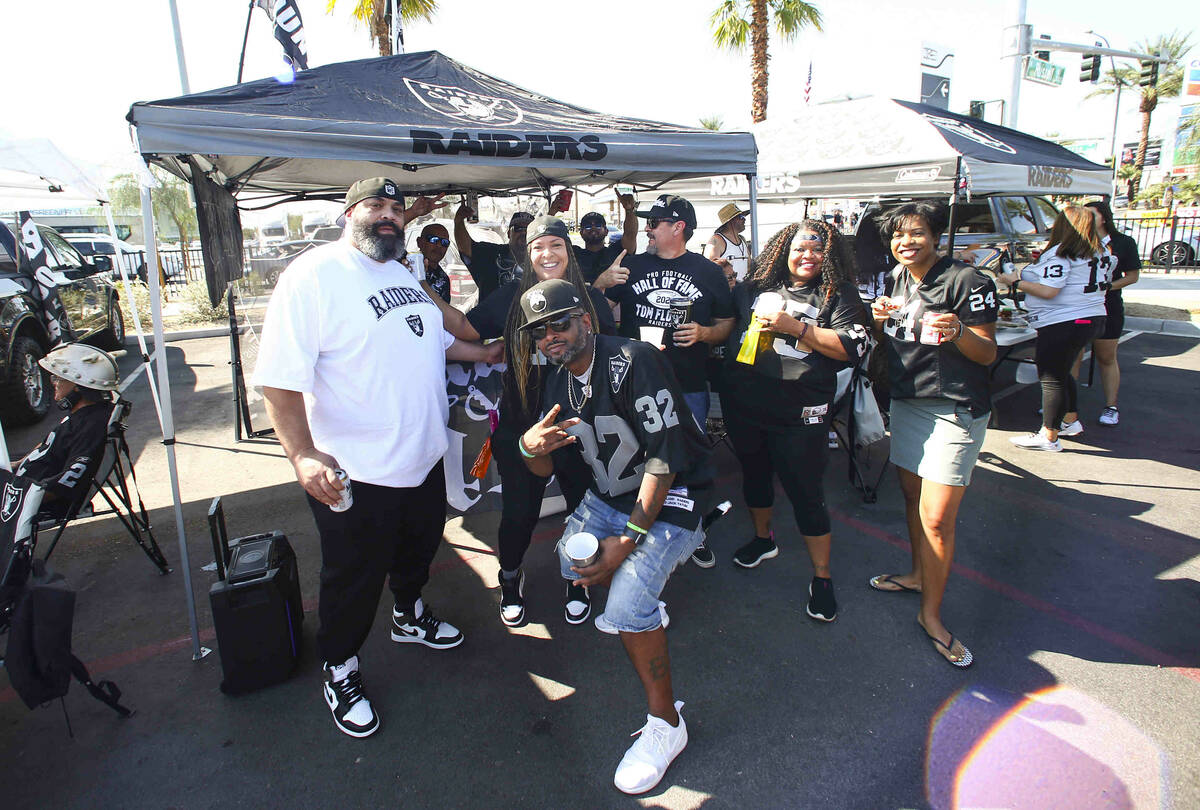 Raiders fans pose for a picture during a tailgate before an NFL game between the Raiders and Mi ...