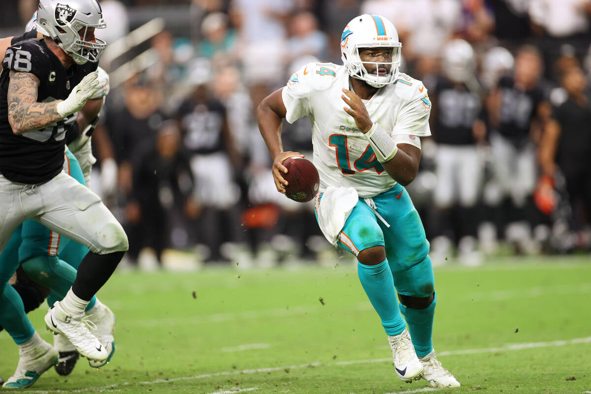 Miami Dolphins quarterback Jacoby Brissett (14) runs for a touchdown under pressure from Las Ve ...