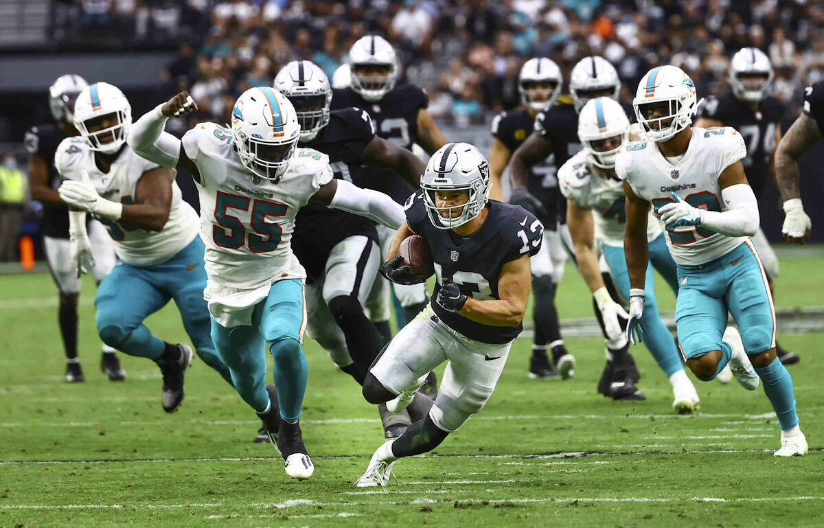 Raiders wide receiver Hunter Renfrow (13) runs the ball under pressure from Miami Dolphins outs ...