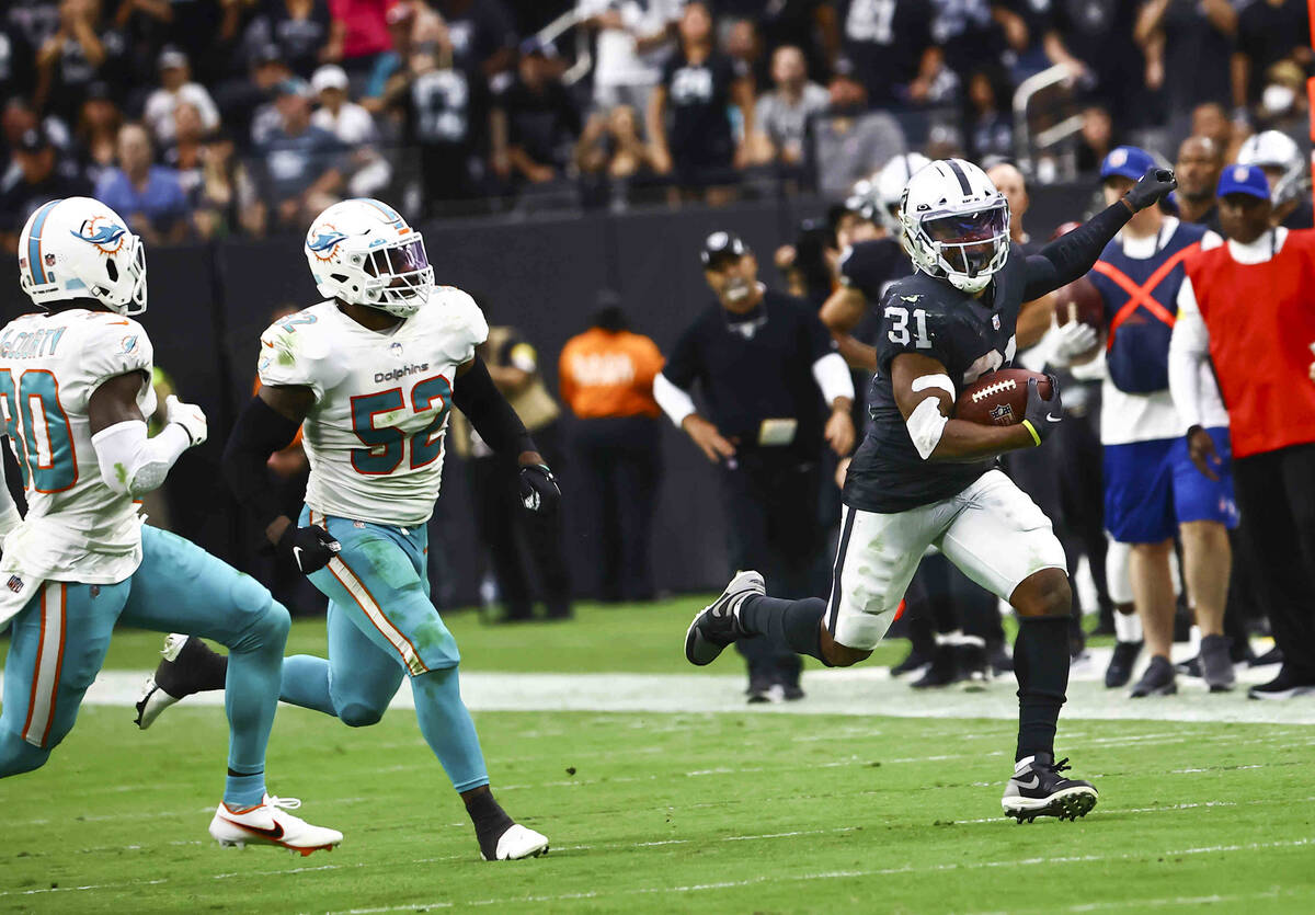 Raiders running back Peyton Barber (31) runs the ball in front of Miami Dolphins middle linebac ...