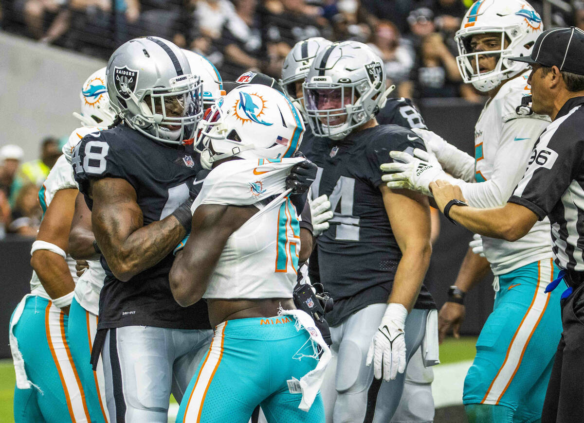 Raiders (48) gets in a fight in the end zone with Miami Dolphins wide receiver Jakeem Grant (19 ...
