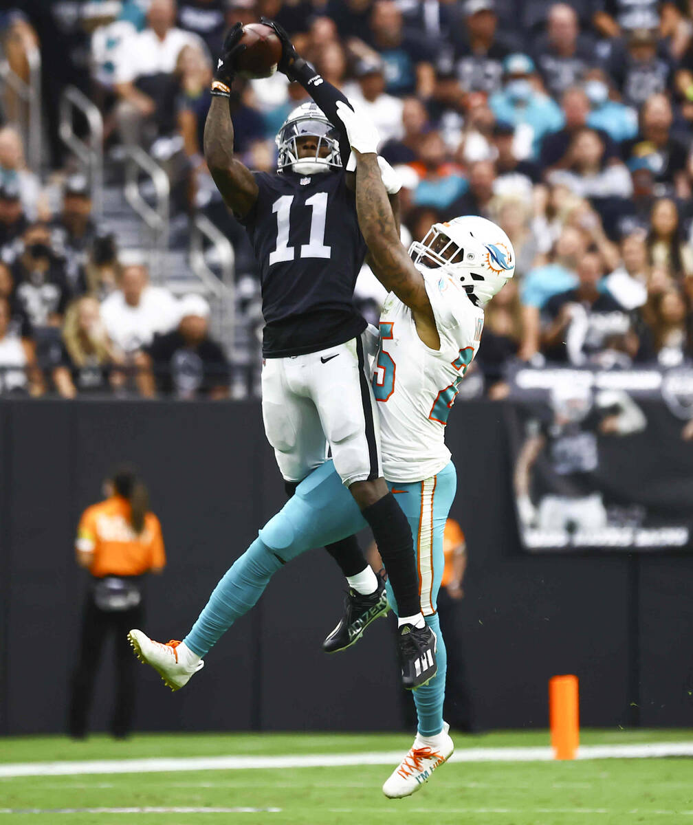 Las Vegas Raiders wide receiver Henry Ruggs III (11) goes up for a 23-yard pass under pressure ...